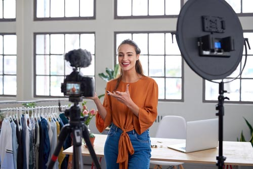 Woman in front of camera showing how to become an influencer and earn money