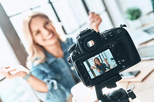 Woman in front of a camera showing what is influencer marketing